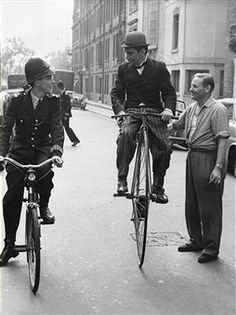 Mexican comic-actor Cantinflas (1911 - 1993) practises on his penny-farthing bicycle for a scene in 'Around the World in Eighty Days', 26th August 1955. He is stopped by a bemused PC Wood in London's Chelsea area.