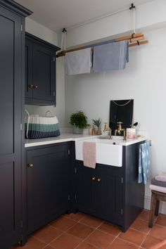 Utility room with ceiling mounted laundry pulley drying rack, ceramic sink, antiqued brass taps, terracotta floor tiles and kitchen units in pantry blue by Devol. By Alison Anderson Interiors Drying Rack Laundry, Clothes Drying Racks, Teracotta Floor, Utility Room Sinks, Boot Room Utility, Drying Room, Pantry Room, Laundry Design, Room Tiles