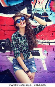 beautiful teenage girl posing near graffiti wall. Urban outdoors,  teenager's lifestyle; denim shorts