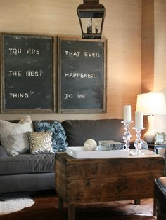"What a clever, loving and economical focal point to this beautiful room. The room is simple, like colonial Shaker. The ""chalkboard"", hanging lantern, the hide rug and the rustic chest type coffee table makes the whole experience feel colonial. The sofa, end table and the table lamp are very contemporary. Design by Anissa Darnell"