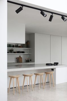 Rolies + Dubois | Loft in Antwerp minimal kitchen with breakfast bar and wooden bar stools