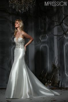 This sophisticated trumpet silhouette wedding dress in mikado features a plunging sweetheart neckline with tulle inset, beaded strapless bodice, princess seams, and a chapel length train.