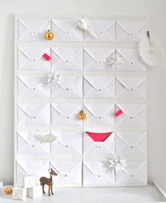 White envelope advent calendar with pops of neon and metallics.   Turn it into the shape of Christmas tree and it will be very easy for you to give away your gifts if you have name printed on the leave of the envelopes!