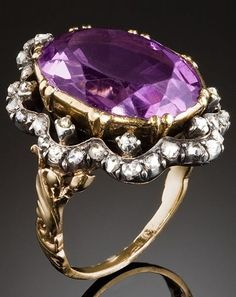 An antique amethyst and diamond ring, 19th century. The central oval faceted amethyst approx. 9 ct. surrounded by rose cut diamonds in a lacy scalloped pattern to a rounded shank with a scroll design on the shoulders set in sterling silver and 18ct. gold. With French import marks. #antique #ring