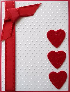 Fairly easy -I embossed a piece of photo paper to give it a little gloss, put it on a red card. I wrapped a satin ribbon around and added a small tied piece. Last, but not least 3 purchased glittered felt hearts...