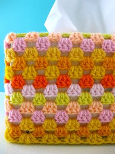 A pile of squares, of the granny variety! Joined into a tube, and voila! one granny square lampshade cover! It slips on and off easily for laundering. The tissue box was looking rather plain and or…