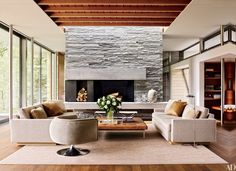 A quartzite chimney breast defines one end of the open-plan living/dining/kitchen area in an Aspen, Colorado, home designed by the architecture firm Bohlin Cywinski Jackson, with interiors by Shelton, Mindel & Associates.