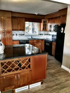 This kitchen renovation features an island with a wine rack, recessed panel cabinet doors, black quartz countertops, and laminate flooring. Black Quartz Countertops, Stone Countertops, Kitchen Reno, Laminate Flooring, Cabinet Doors, Plumbing, Wine Rack, Island, Home Decor