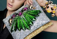 """London-based brand Mawi has unveiled its latest collection and another new route – a foray into luxury clutch bags, designed to mimic its crystal-set costume jewellery. The collection, designed for SS13, made its debut at London Fashion Week in September.    The range of clutch bags feature glitter, neon colours, and structural elements. The bags are embellished with Perspex spikes and metal elements."" - Professional Jeweler"