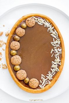 Mazurek kajmakowy Tart with butterscotch filling and decorated with amaretti cookies and almond slices