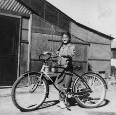 Grace Toya with bicycle at the Tule Lake internment camp, 1945