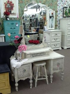 $250 - This is an antique three drawer vanity, with bling knobs, and applied roses. The vanity comes complete with large original mirror, casters, and a small stool. The set has been painted and distressed. The vanity measures 44 inches across the front, 18 inches deep and 64 inches to the top of the mirror. It can be seen in booth H13 at Main Street Antique Mall 7260 East Main St ( E of Power Rd ) Mesa 85207  480 9241122 open 7 days 10 till 530 Cash or charge 30 day layaway also available