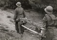 GERDA TARO:  Two Republican soldiers with a soldier on a stretcher, Navacerrada Pass, Segovia front, Spain. Late May-early June 1937.  Gelatin silver print.