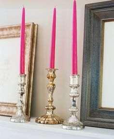 Silver and gold candlesticks with hot pink tapers decorate a traditional mantel.