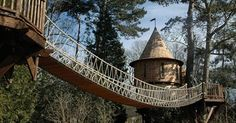 "Thanks to the British design firm Blue Forest, a family is ""Living the High Life"" in one of the coolest tree houses you'll ever see. While it has a medieval-influenced architectural style, this tree house is anything but old school. There haven't been many homes (on or off the ground) that feature a rope bridge, zip line, and…"