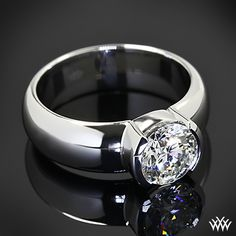 Heavy Half-Bezel Solitaire Engagement Ring is set in platinum and holds a beautiful 1.36ct Round Brilliant Diamond.