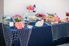 Food station with navy blue tablecloth and netting for nautical ocean theme baby shower