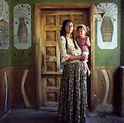 A Roma woman and child stand in front of a painted wall in a house, in the old part of the Sintesti Roma camp.	  Filename: 200409_GYP 40714.jpg  Copyright Jeremy Sutton-Hibbert
