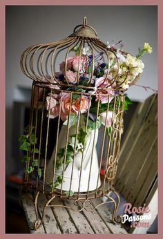 Combination of flowers and antique bird cage...I like it.  Dried flowers could add to the vintage feel and make the display last longer.