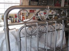 used Rustoleum spray paint to give an old brass bed new life - gray hammered metal