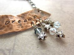 """Hammered copper inspirational necklace stamped """"Follow your Dreams.""""  Swarovski crystal beads and silver stars dangle from the bottom. $36"""