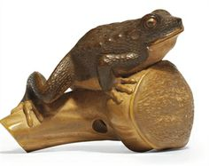 A WOOD NETSUKE SIGNED 'SUKENAGA', MEIJI PERIOD, LATE 19TH CENTURY Of a toad on a lotus pod 2 in. (5 cm.) long