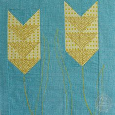 After the block was pieced, we placed stabilizer/tear away behind it and used wool Aurifil thread and a stitch length of 3 to stitch the stem and some ...