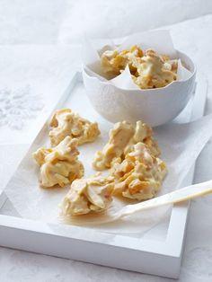 Weiße Schoko Crossies  Zutaten (48 Stück)  500 g weiße Kuvertüre, 125 getrocknete Soft-Aprikosen, 100 g Mandelstifte, 50 g Cornflakes, Backpapier