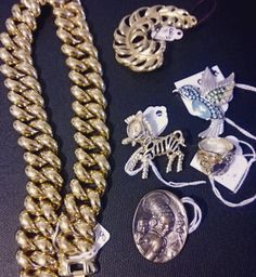Some vintage pieces: a necklace, brooches, and a ring.