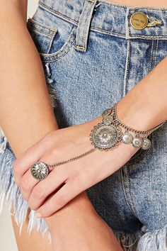 A midweight hand chain featuring burnished and etched medallion designs on the bracelets and rings.