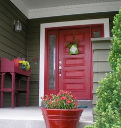 like the boldness of the red door and accessories against the green house