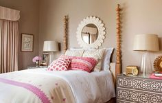 Nailhead-detailed bedside chests add textural interest to this master bedroom. The colorful bedding, twisted posters, and mirror above lend a touch of carefree charm - Traditional Home®  Photo: John Ellis Design: Carmen Lopez