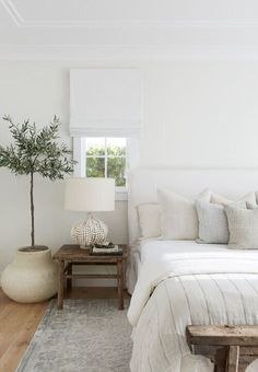 White slipcovered headboard bed features a linen bedding and linen pillows besid. - White slipcovered headboard bed features a linen bedding and linen pillows beside a potted olive tr - Slipcovered Headboard, Cream Headboard, Linen Headboard, Headboards, Suites, Interior Modern, White Interior Design, Natural Interior, Simple Interior