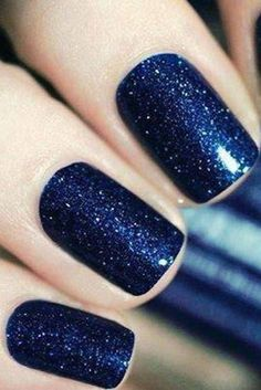 Red and green aren't the only holiday-appropriate shades. A rich navy blue with silver shimmer is a vibrant way to wear glitter for Christmas. Click through for more unique nail designs and colors that are perfect for your Christmas mani.