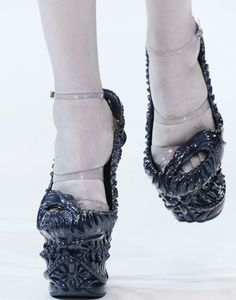 Alexander McQueen  --  Plastic straps to keep the shoes on, without them it hardly could be called a shoe!