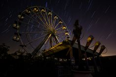 Long exposure star trails photographed in front of the Ferris wheel at the abandoned Six Flags New Orleans theme park [2048x1365][OC]