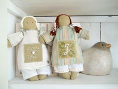 two selfmade dolls with small sampler on their gowns