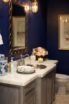 Beautiful bathroom features navy walls as a backdrop for gold oval chain link mirror flanked by maritime sconces over gray washstand topped with white marble framing round, metal sink and hook spout faucet.