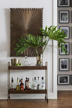 This+dining+room+features+a+timeless+bar+car+positioned+in+front+of+a+large+wooden+wall+sculpture.+Just+around+the+corner+is+a+gallery+wall+with+framed+black+and+white+photographs.+