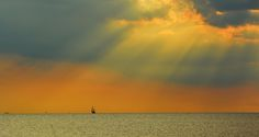 Wind Waves and Water Sports Category.  The suns rays pointing toward the sailboat on the horizon. Nags Head. Summer.