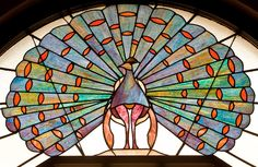 Photograph of vintage stained glass peacock fanlight above the entry of the 1928 Hotel Baker in St. Stained Glass Birds, Stained Glass Patterns, Stained Glass Windows, Leaded Glass, Mosaic Glass, Peacock Decor, Light Bulb Lamp, Through The Looking Glass, Geometric Shapes