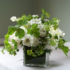 garden inspired centerpiece containing hydrangea, roses, mini callas, scabiosa, waxflower, bupleurum, and scented geranium with an aspidistra leaf wrap tucked into the vase