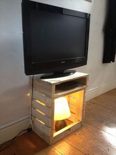 Find and clean up an old wooden crate for a TV stand...great idea. In the photo here it looks like someone who could build things added a shelf..but for those of us who have no brains for stuff like that...a simple pallet would work :)