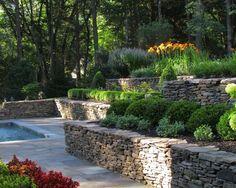 un mur en pierre naturelle autour de la piscine