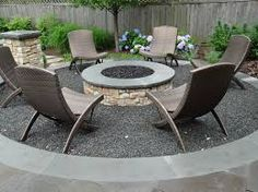 A round, masonry gas-fired fire pit clad in natural stone. It sits in a sunken bluestone chip circle, contained by custom bluestone coping. The fire pit itself is coped with natural bluestone and filled with black lava rock. Fire Pit Bbq, Small Fire Pit, Modern Fire Pit, Round Fire Pit, Fire Pit Area, Diy Fire Pit, Fire Pit Backyard, Backyard Patio, Pergola Patio