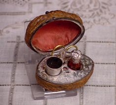 """Miniature Walnut Etui - Miniature etuis were a very popular novelty in the second half of the 19th century. Made from an actual walnut, this wonderful little etui is fitted with beautiful etched silver.   The lid is lined with silk.  The tools inside include a gorgeous red crystal scent bottle with an etched silver lid, a silver thimble and needlecase and really tiny pair of gilt scissors.  The walnut measures 2"""" x 1 1/2"""" x 1 3/4"""" high."""