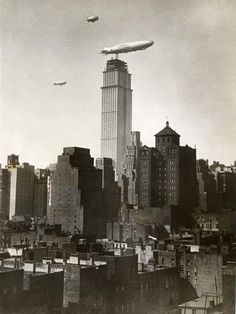 The airship, Los Angeles, hovers near an incomplete Empire State Building. New York, 1930