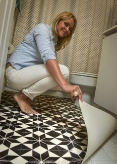 Trade out a tacky bathroom floor without a renovation. Using a box cutter, Huerta cut a $260 vinyl floor cloth to fit the bathroom floor exactly and simply laid it on top of the cracked tiles. The black-and-white Stargazer pattern is by Spicher and Co.