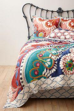 Metallinen sängynpääty. Värikäsk koristeellinen päiväpeitto.