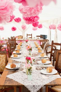 Pink pompoms hanging in a wedding marquee, with rustic/vintage tables and mismatched chairs.  From 'A Cymbeline Gown And Coral Pink Peonies For A DIY, Modern Vintage Wedding in France' on www.lovemydress.net  Photography - http://www.pearl-pictures.com/ Bride - http://91magazine.co.uk/